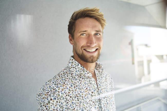 Porträt eines glücklichen jungen Mannes im gemusterten Hemd — Stockfoto