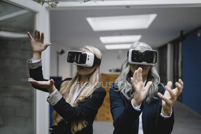 Mature and young businesswoman wearing VR glasses — Stock Photo