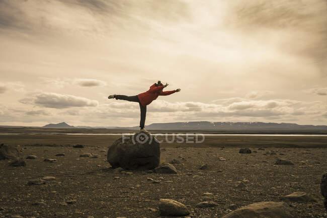 Молода жінка балансує на одній нозі на скелі в вулканічних високогір