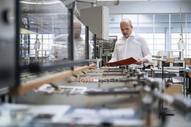 Бізнесмен на друкарні перевіряє продукт. — стокове фото