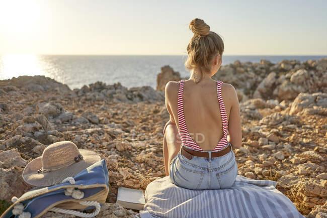 Junge Frau sitzt am felsigen Strand, entspannend, Menorca, Spanien — Stockfoto