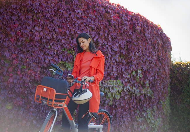 Молода жінка активує орендний велосипед за допомогою смартфона. — стокове фото