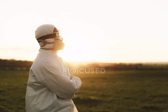 Hombre con traje protector y máscara en el campo al atardecer - foto de stock