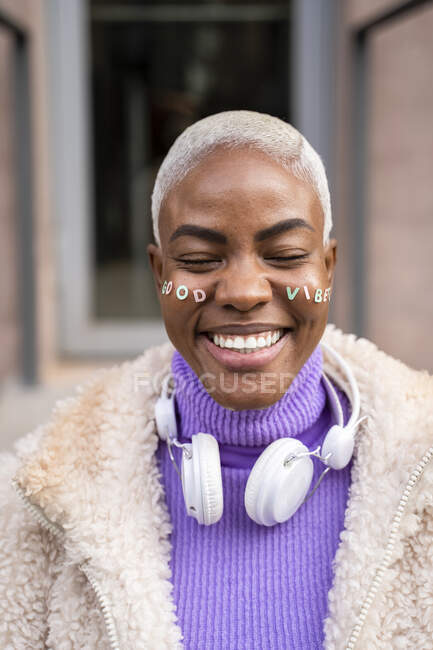 Portrait of mature white haired woman with white headphones and stickers in her face, good vibes — Stock Photo