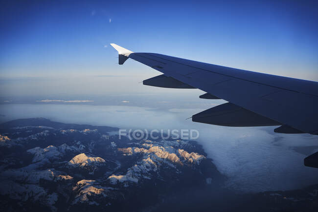 France, Auvergne-Rhone-Alpes, Wing of Airbus A321 літає над європейськими Альпами і Женевським озером на світанку. — стокове фото