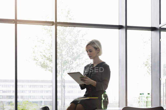 Businesswoman sitting on meeting table using digital tablet — Stock Photo