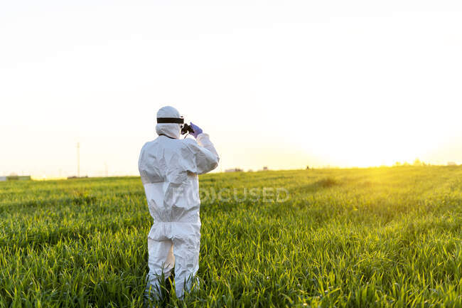 Female scientist researching in field and looking through binoculars at sunset — Stock Photo