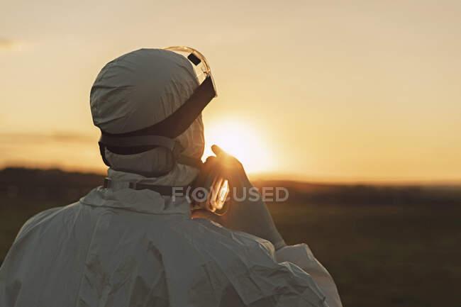 Vista trasera del hombre con traje protector y máscara en el campo al atardecer - foto de stock