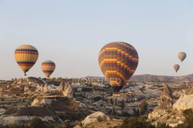 Colorful hot air balloons flying over landscape against clear sky at Cappadocia, Turkey — Stock Photo