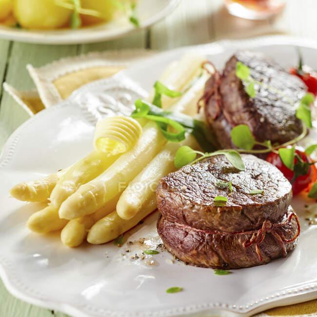 Espárragos blancos y filete de res en plato en restaurante - foto de stock