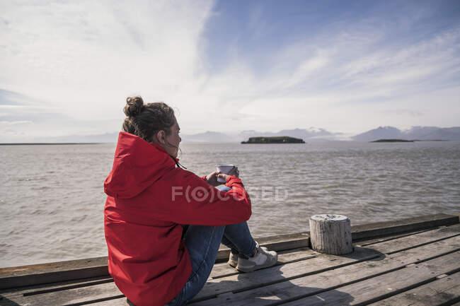 Молода жінка, що сидить на пристані, п