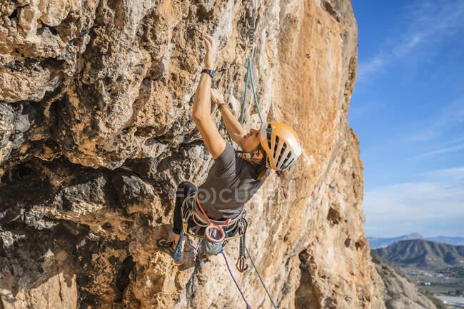 Mulher escalando no rosto de rocha — Fotografia de Stock