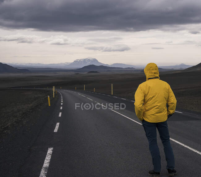 Man standing at  empty road, looking at distance, Iceland — Stock Photo