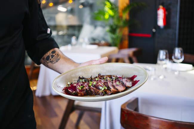 Крупный план человека, подающего блюдо в ресторане — стоковое фото