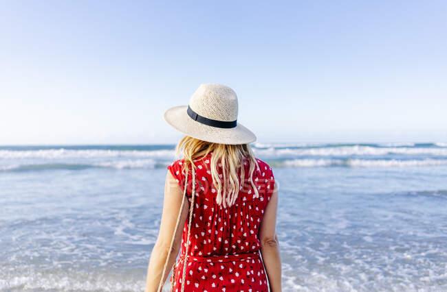 Mujer rubia vestida de rojo y sombrero y caminando por la playa, Playa de Las Catedrales, España - foto de stock