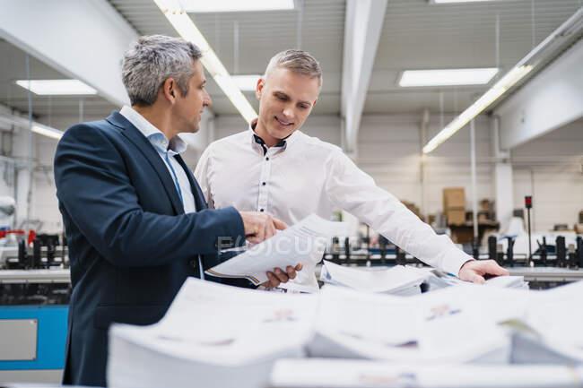 Два бізнесмени обговорюють папір на фабриці. — стокове фото