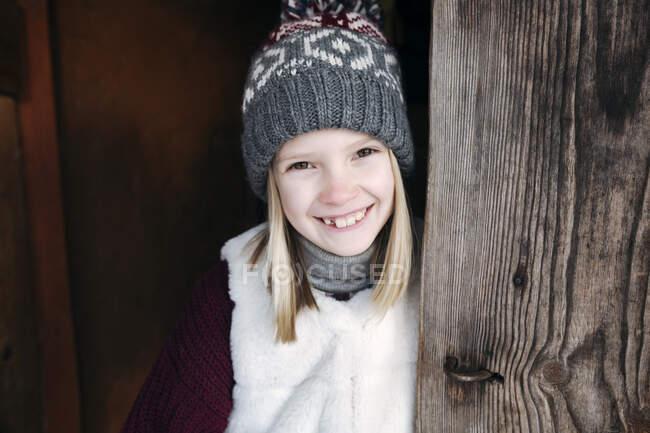Ritratto di ragazza felice che indossa un cappello di lana al muro di legno — Foto stock