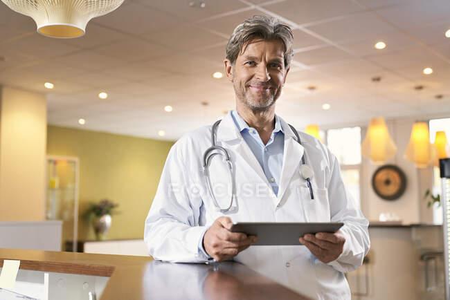 Retrato de médico confiado con tableta en recepción en su práctica médica - foto de stock