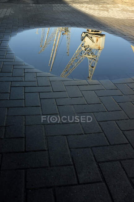 Germany, Old industrial cranes reflecting in shiny puddle — Stock Photo