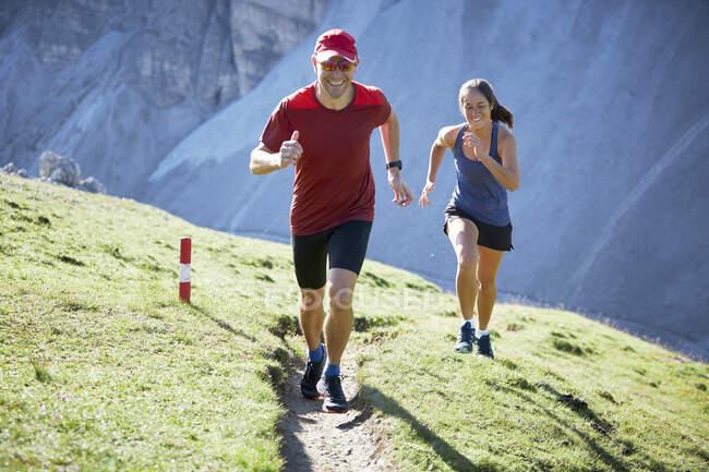 Мужчина и женщина бегут в горы — стоковое фото