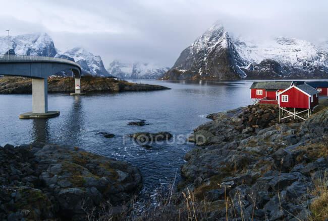 Ponte e capanne rosse sulla costa, Hamnoy, Lofoten, Norvegia — Foto stock
