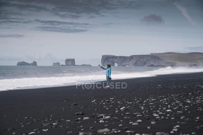 Молода жінка фотографує лавовий пляж в Ісландії. — стокове фото