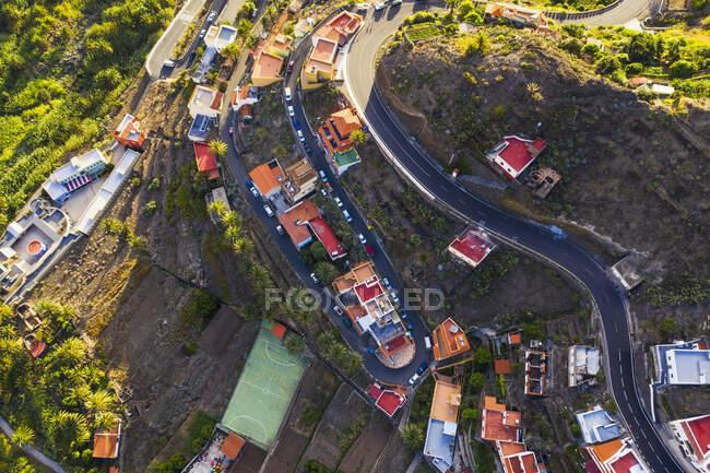 España, Islas Canarias, La Gomera, Valle Gran Rey, El Retamal, Vista aérea de la ciudad y caminos en el paisaje de montaña - foto de stock
