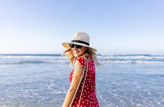 Donna bionda che indossa vestito rosso e cappello in spiaggia, girando e guardando la fotocamera — Foto stock