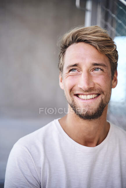 Portrait of smiling young man wearing white t-shirt — Stock Photo