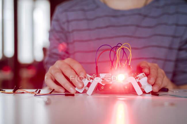 Robot de montaje a mano de niño, luz roja - foto de stock