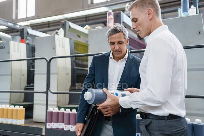 Два бизнесмена изучают продукт на фабрике — стоковое фото