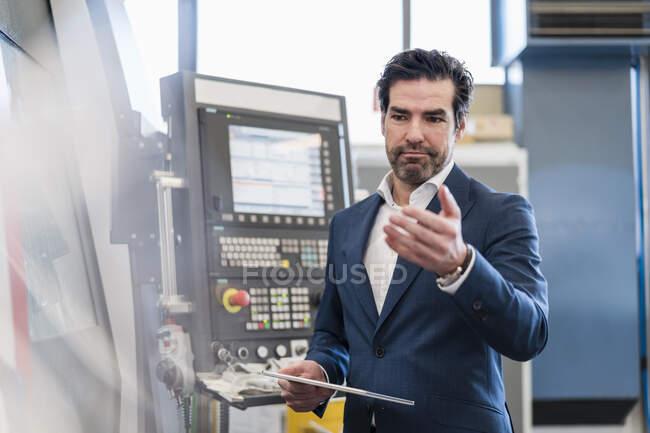Empresário usando tablet em uma máquina em uma fábrica — Fotografia de Stock