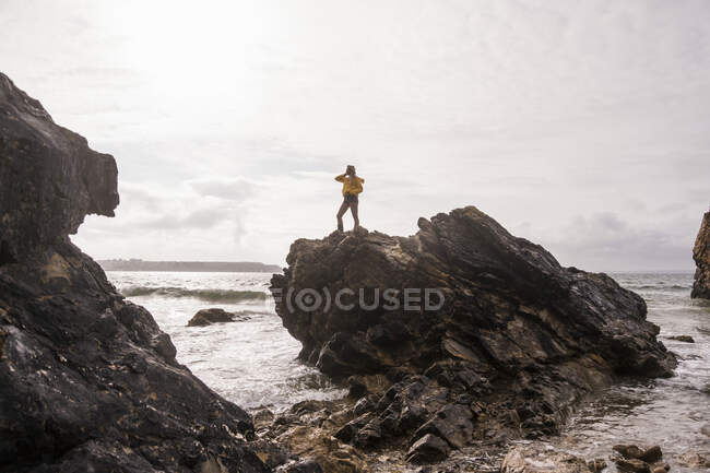 Woman wearing yellow rain jacket standing at rocky beach — Stock Photo