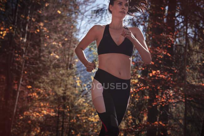 Жінка біжить осіннім лісом. — стокове фото