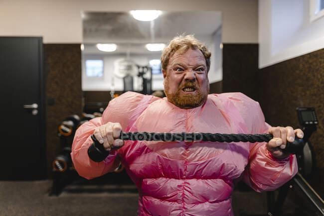 Hombre con traje de culturista rosa practicando en el gimnasio - foto de stock