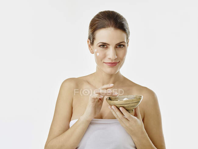 Retrato de mujer sonriente con cuenco de crema hidratante sobre fondo blanco - foto de stock