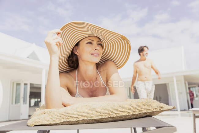 Mujer relajándose en la tumbona con el hombre en el fondo - foto de stock