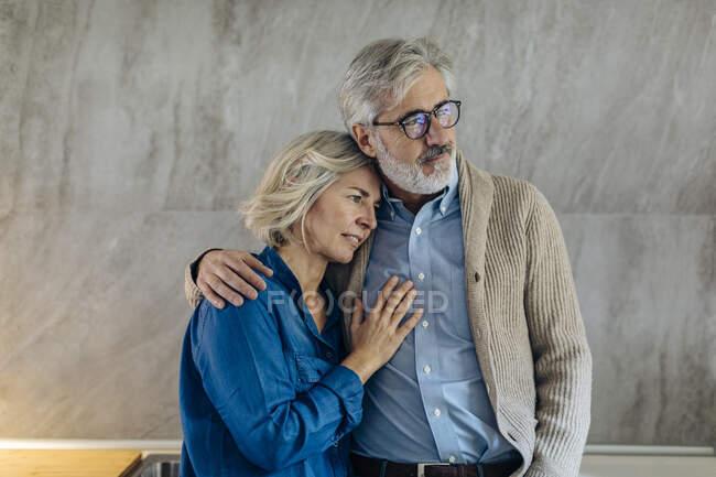 Сердечна зріла пара, яка обіймає сім