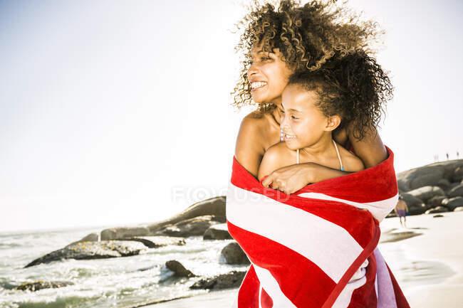 Madre e figlia felici avvolti in un asciugamano sulla spiaggia — Foto stock