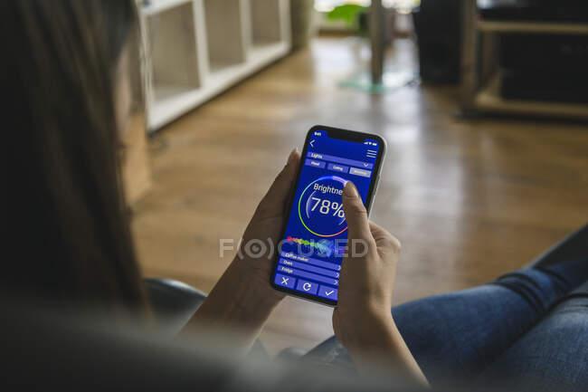Mujer joven con teléfono inteligente con funciones de control del hogar inteligente - foto de stock