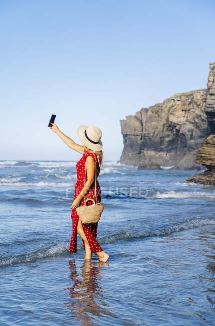 Donna bionda vestita di rosso e cappello e con smartphone in spiaggia — Foto stock