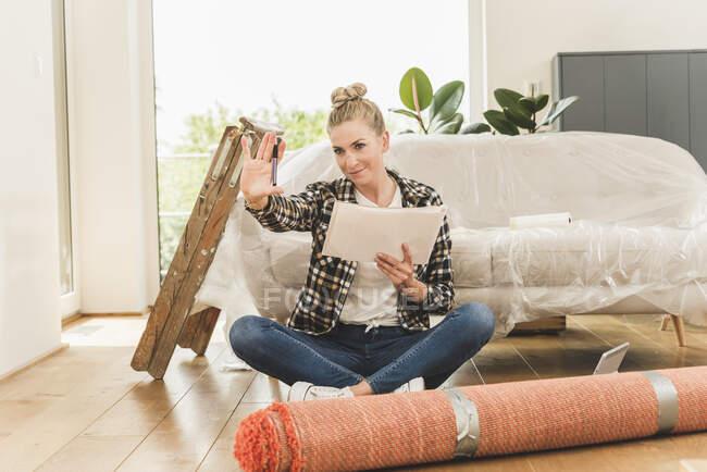 Жінка сидить на підлозі в новому домі і піднімає руку. — стокове фото