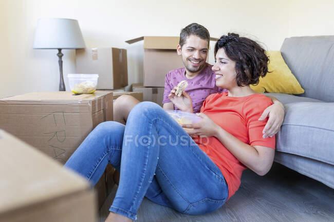 Счастливая пара переезжает в новый дом, отдыхает и обедает — стоковое фото