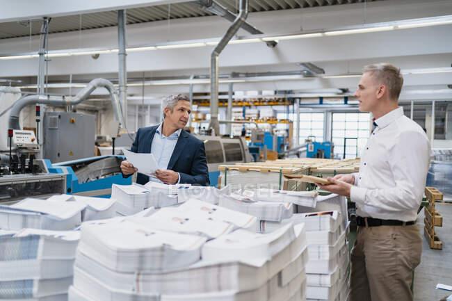 Два бізнесмени розмовляють на фабриці. — стокове фото