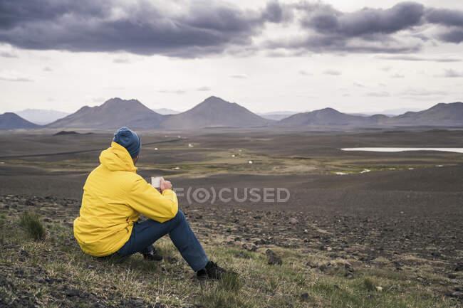 Homem bebendo café, olhando para a paisagem na Islândia — Fotografia de Stock