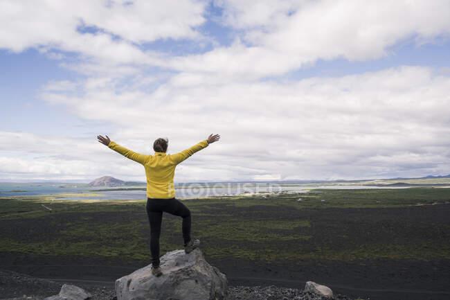 Mujer joven parada en el cráter Hverfjall cerca de Myvatn, Islandia, con los brazos extendidos - foto de stock