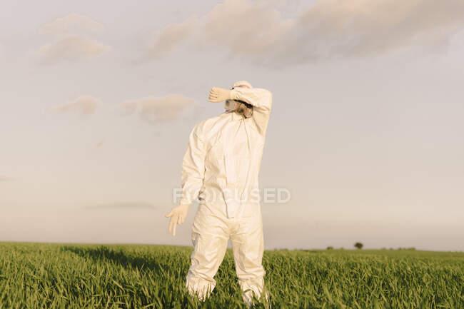 Hombre con traje protector y máscara en el campo cubriendo sus ojos - foto de stock