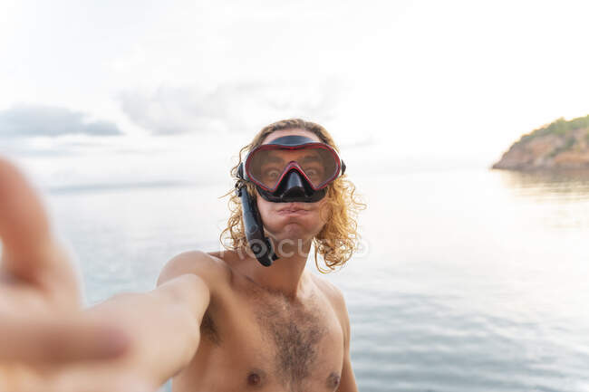 Giovane con snorkeling fare una faccia sulla spiaggia — Foto stock
