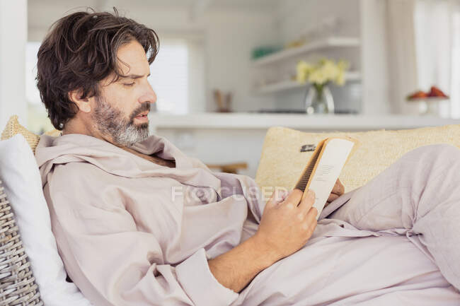 Hombre relajado en albornoz leyendo un libro - foto de stock