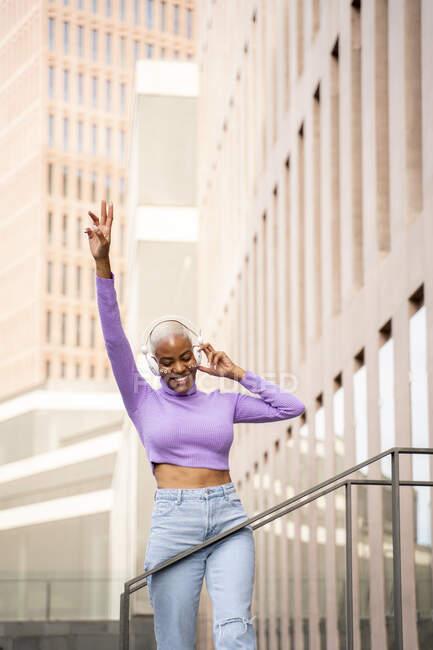 Retrato de mujer de pelo blanco con auriculares blancos escuchando música y bailando en la ciudad - foto de stock
